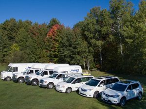 The Furnace Dr's Fleet of vehicles parked in the grass.